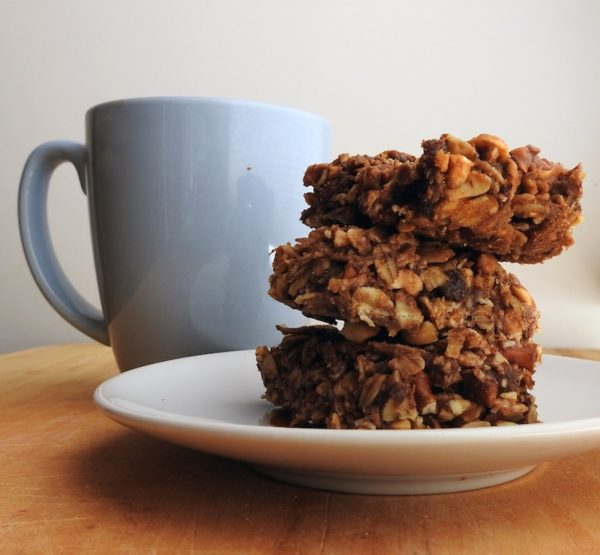 stack of three peanut butter-banana granola bars on a plate next to a coffee mug